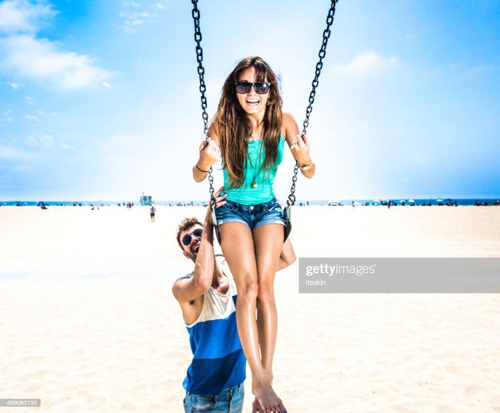 Couple teetering on swings LA beach : Stock Photo