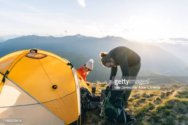 couple tent camping on mountain top, reaching into backpack in sunset light - heterosexual couple stock pictures, royalty-free photos & images