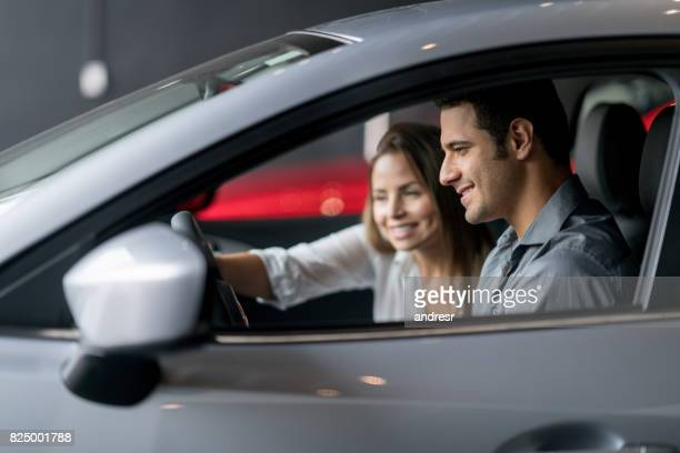couple test driving a car at the dealership - test drive stock pictures, royalty-free photos & images