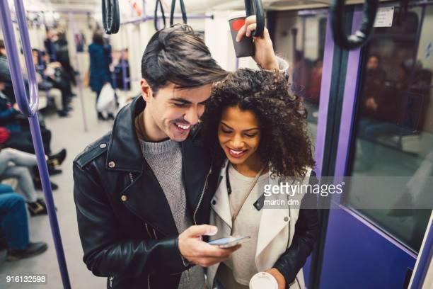 enviar mensajes de texto pareja en el metro - vertical red tube fotografías e imágenes de stock