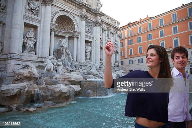 couple throwing a coin in the Trevi Fountain Rome