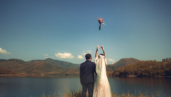 Couple Throwing Bouquet While Standing At Lakeshore Against Sky - gettyimageskorea
