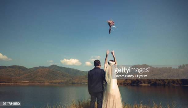 couple throwing bouquet while standing at lakeshore against sky - wedding ceremony stock photos and pictures