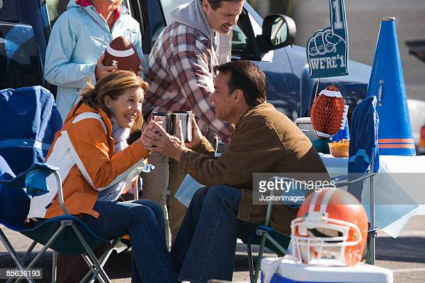 Couple toasting at tailgate party