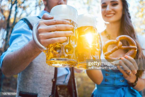 couple toasting beer glasses while standing outdoors - oktoberfest stock pictures, royalty-free photos & images