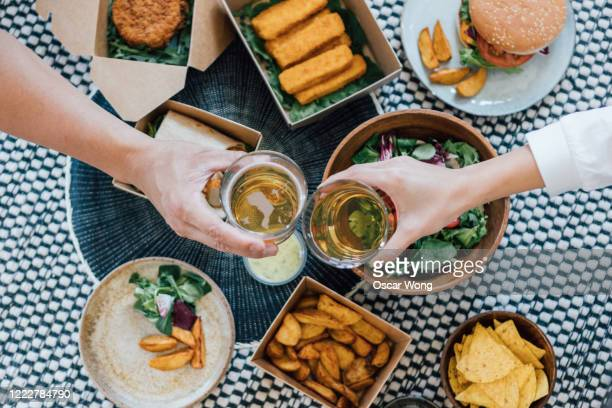 couple toasting beer while eating takeaway food - alcohol stock pictures, royalty-free photos & images