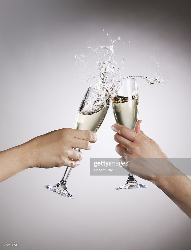 Couple toasting champagne flutes and spilling : Stock Photo