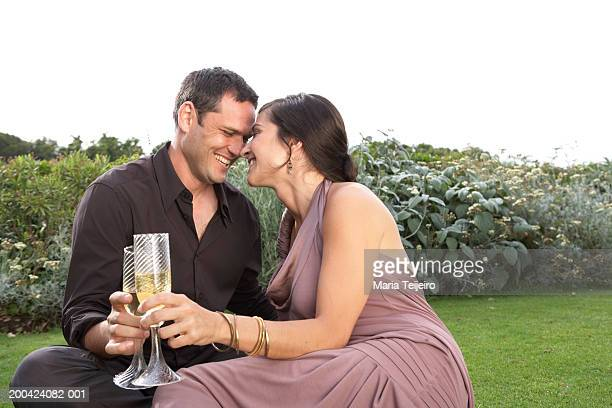 Couple toasting champagne on grass, rubbing noses, smiling, close-up