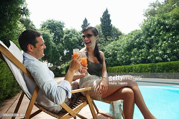 Couple toasting drinks on sun lounger by outdoor pool, smiling