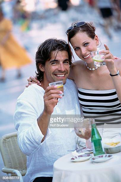 Couple toasting each other at sidewalk cafe
