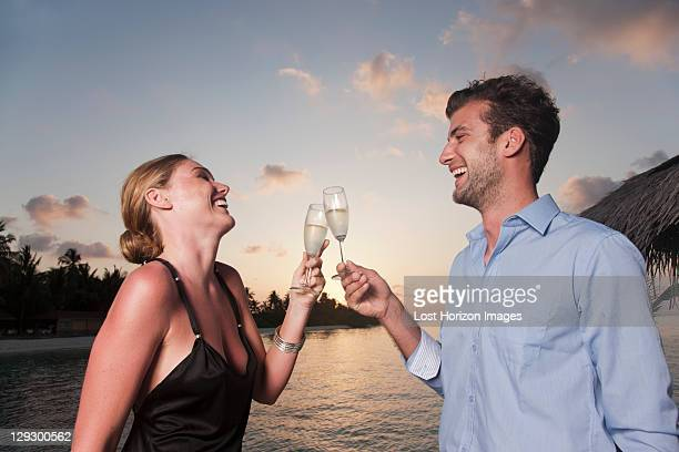 Couple toasting each other on dock