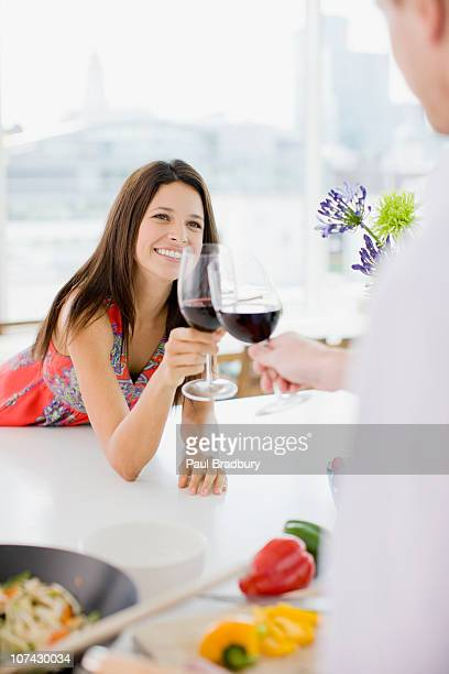 Couple toasting in kitchen with red wine