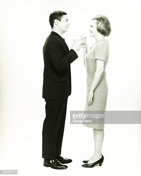 Couple portant un toast en studio, (B & W