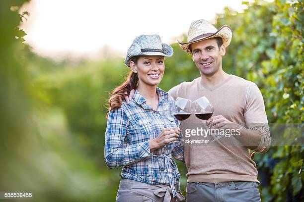 Couple toasting in vineyard.