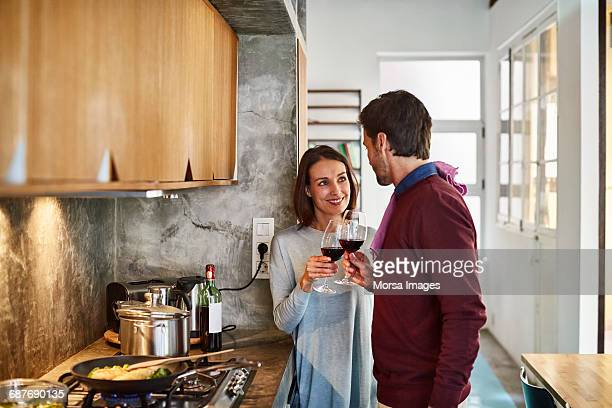 Couple toasting wine glasses at kitchen counter