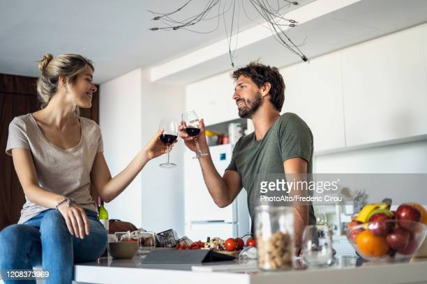 couple toasting wine glasses in kitchen - celebratory toast stock pictures, royalty-free photos & images