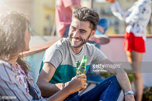 Couple toasting with beers at rooftop party
