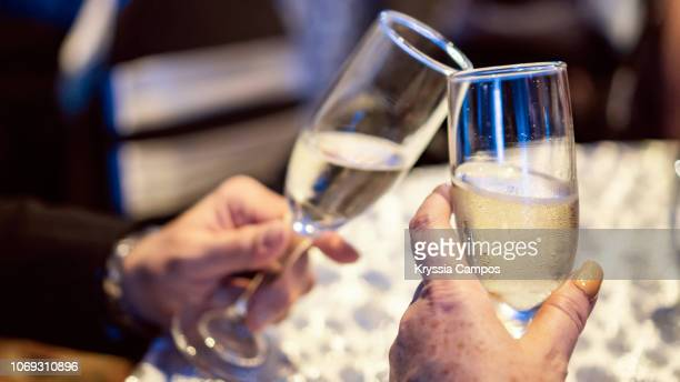 couple toasting with champagne at party - 新年レセプション ストックフォトと画像