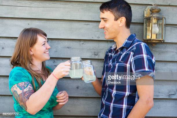 Couple toasting with drinks near wall
