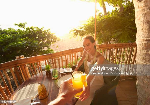 Couple toasting with orange juice on patio