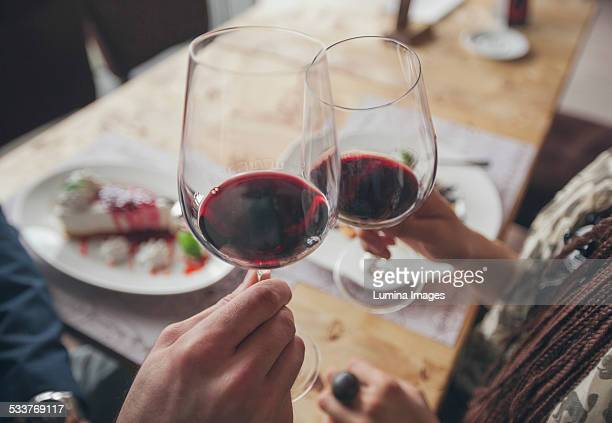 couple toasting with wine in cafe - brindisi bicchieri foto e immagini stock