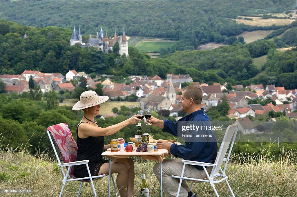 Couple toasting with wing, Castle and village of La Rochepot in background, side view : Stock Photo