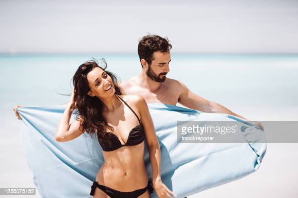 couple together at seaside with towel - hot wives photos stock pictures, royalty-free photos & images