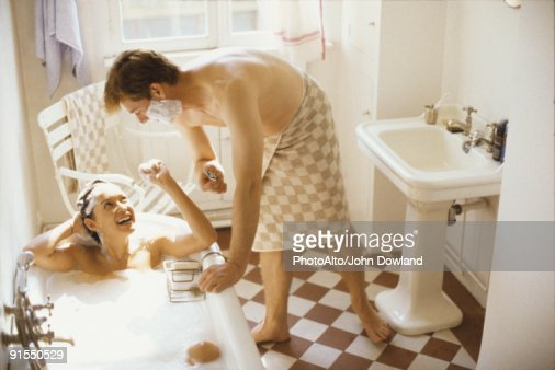 Couple Together In Bathroom Woman In Bathtub Man Leaning