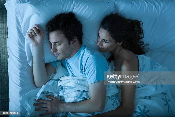 Couple together in bed, woman embracing man, watching him sleep