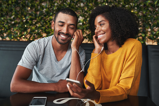 Couple together listening music in cafe smiling 1159441480