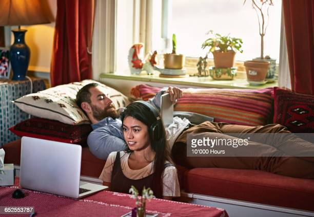 couple together one with ipad one watching laptop - バークシャー州 レディング ストックフォトと画像