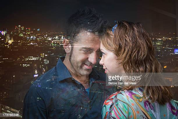 Couple together with city reflections in window.
