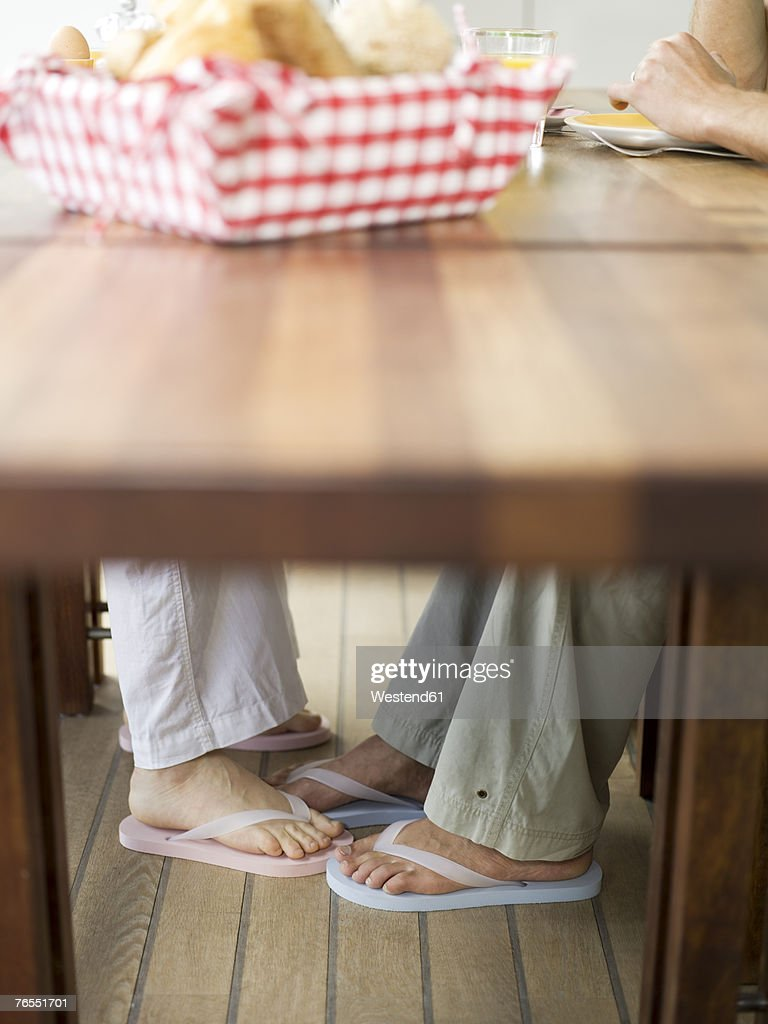 Couple touching feet under table : Stock Photo