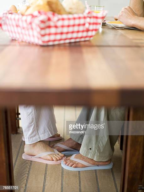 Couple sitting at table, playing footsie
