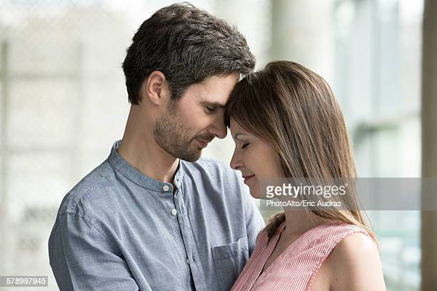 Couple touching foreheads, side view