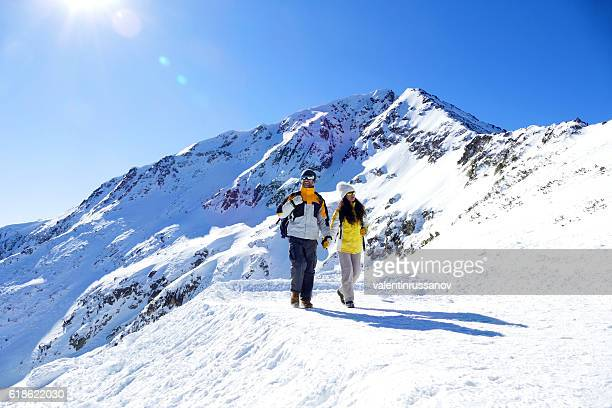 Couple tourists holding hands and walking on snow mountain