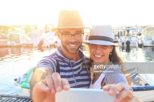 Couple tourists taking selfie on harbor