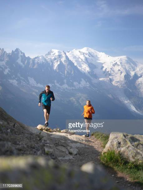 couple trail run through mountains in morning light - auvergne rhône alpes stock pictures, royalty-free photos & images