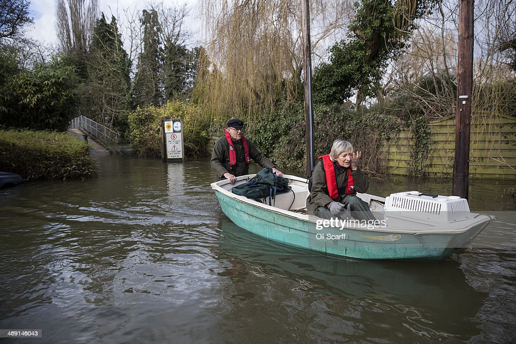 A couple transport their cats to the vet by boat along a flooded road near the River Thames on February 13, 2014 in Wargrave, England.The Environment Agency continues to issue severe flood warnings for a number of areas on the River Thames in the commuter belt west of London. With heavier rains forecast for the coming week people are preparing for the water levels to rise.