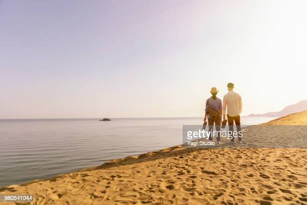 Couple traveler walking in a sand dune looking at the sea