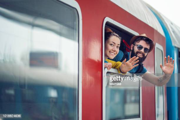 couple travelers waving from the train window - station stock pictures, royalty-free photos & images