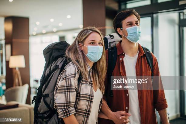 couple travelers with medical masks just arrived in hotel - guest stock pictures, royalty-free photos & images