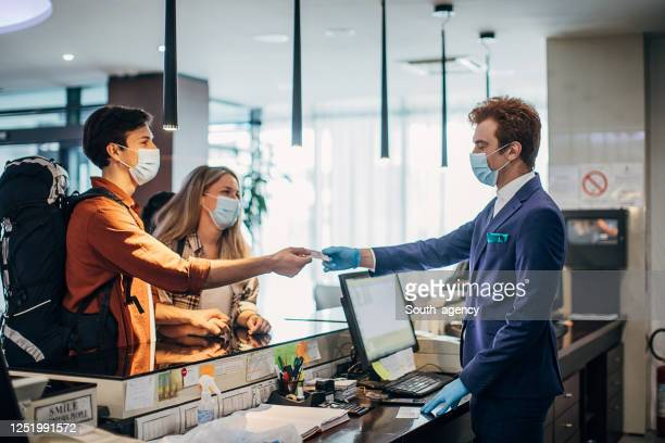 couple travelers with medical masks on hotel reception talking to male receptionist - hotel stock pictures, royalty-free photos & images