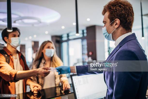 couple travelers with medical masks on hotel reception talking to male receptionist - south_agency stock pictures, royalty-free photos & images