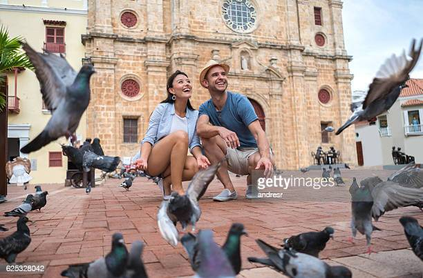 couple traveling and feeding doves in cartagena - cartagena colombia stock photos and pictures