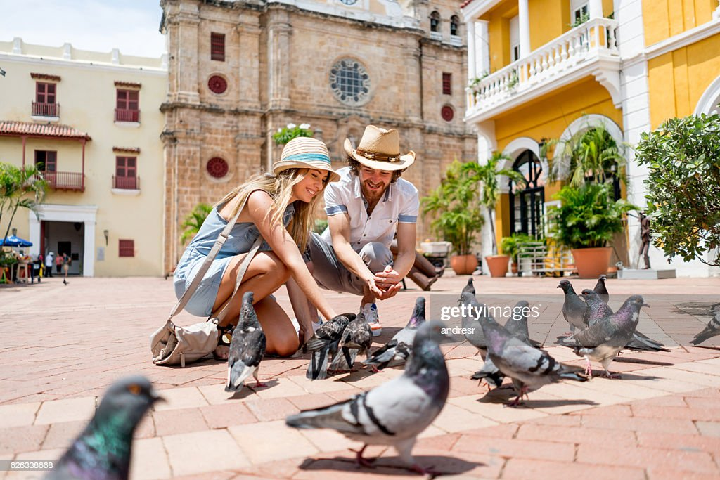 Couple traveling and feeding doves in Cartagena : Foto de stock