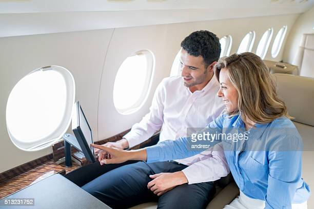 Couple traveling by plane and enjoying onboard entertainment