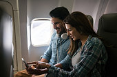 Couple traveling by plane and using their cell phone onboard