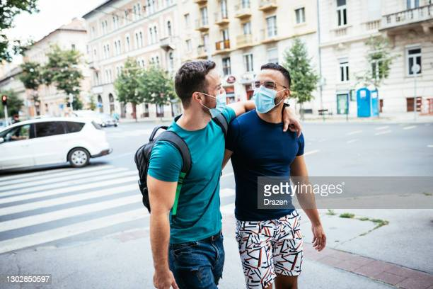 lgbt couple traveling in summer and wearing face masks during coronavirus pandemic - hungary stock pictures, royalty-free photos & images