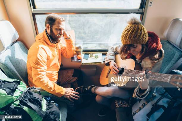 couple traveling in train and playing the guitar - martin dm stock pictures, royalty-free photos & images